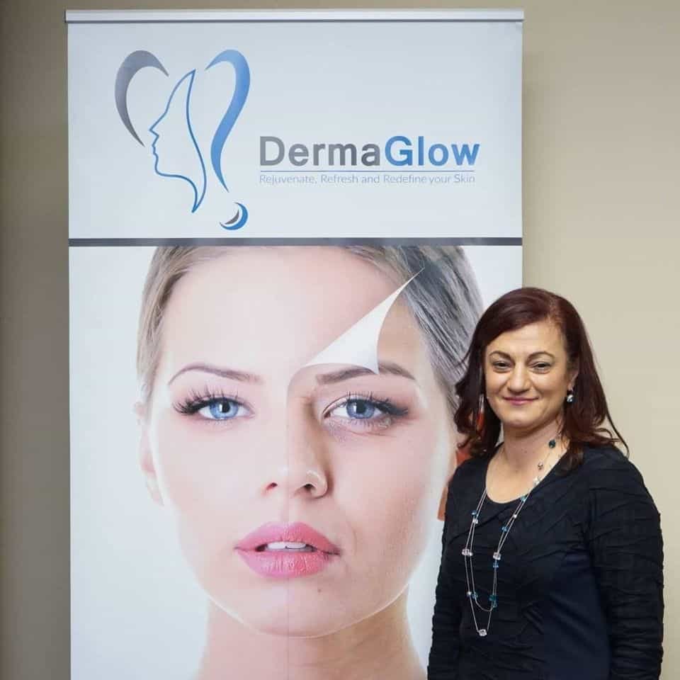 Doctor Maisoon from dermaglow skin clinic standing next to a banner of dermaglow skin clinic